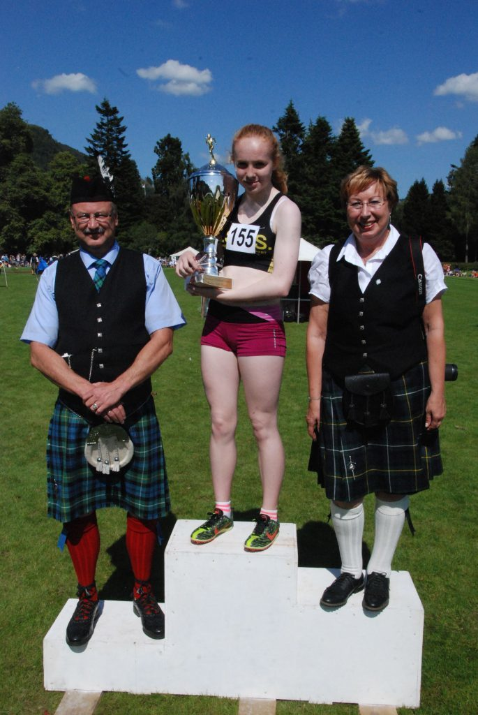 Michael and Susane Enders presenting Laura Ferguson with the Clan Campbell Society Germany Trophy  for the ladies 1600 metre race.