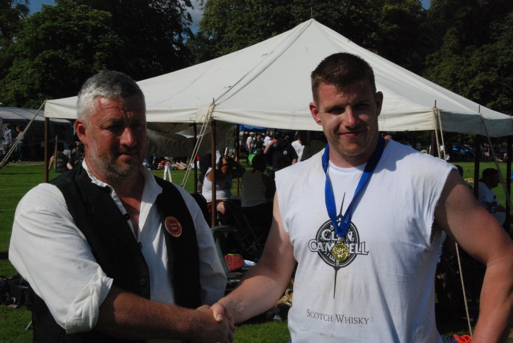Games Convener, Stephen King, presents Lorne Colthart with his World Caber Championship medal.