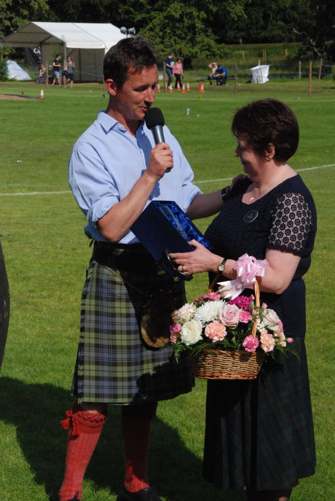 The Duke of Argyll presents Margaret Mather with flowers and a commemorative vase to mark her 26 years of service at the Inveraray Games.