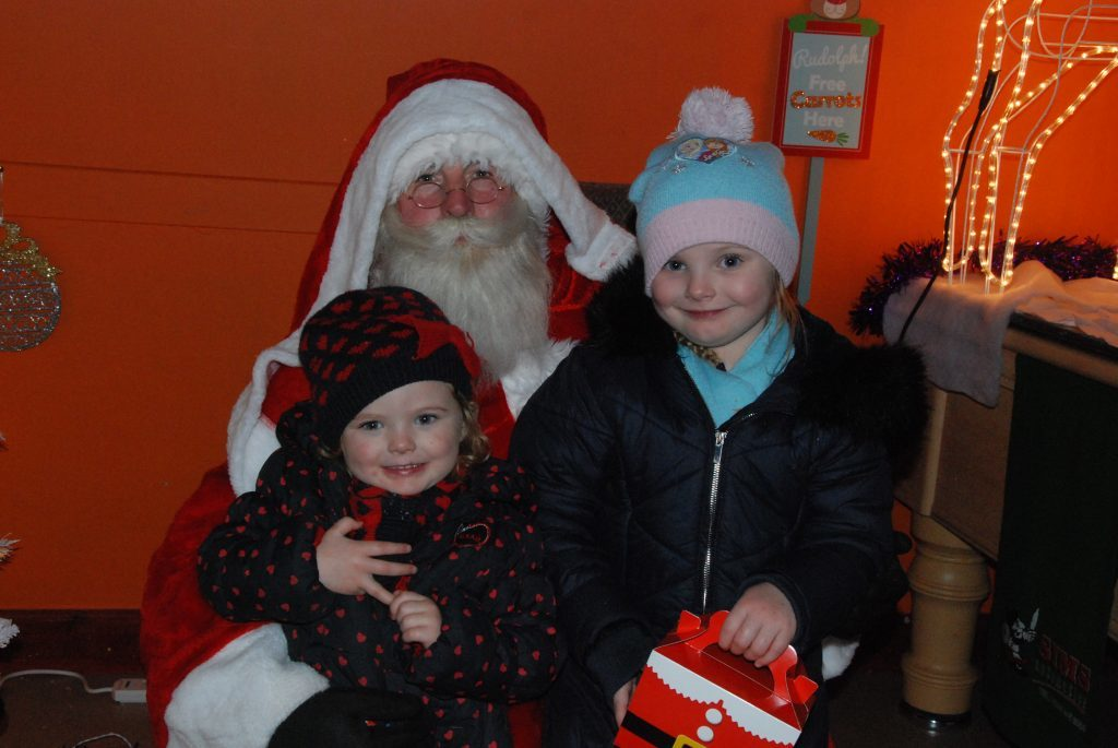 Sisters Carly and Kacey are all smiles as they meet Father Christmas. 08_a49lochgilpheadlights03