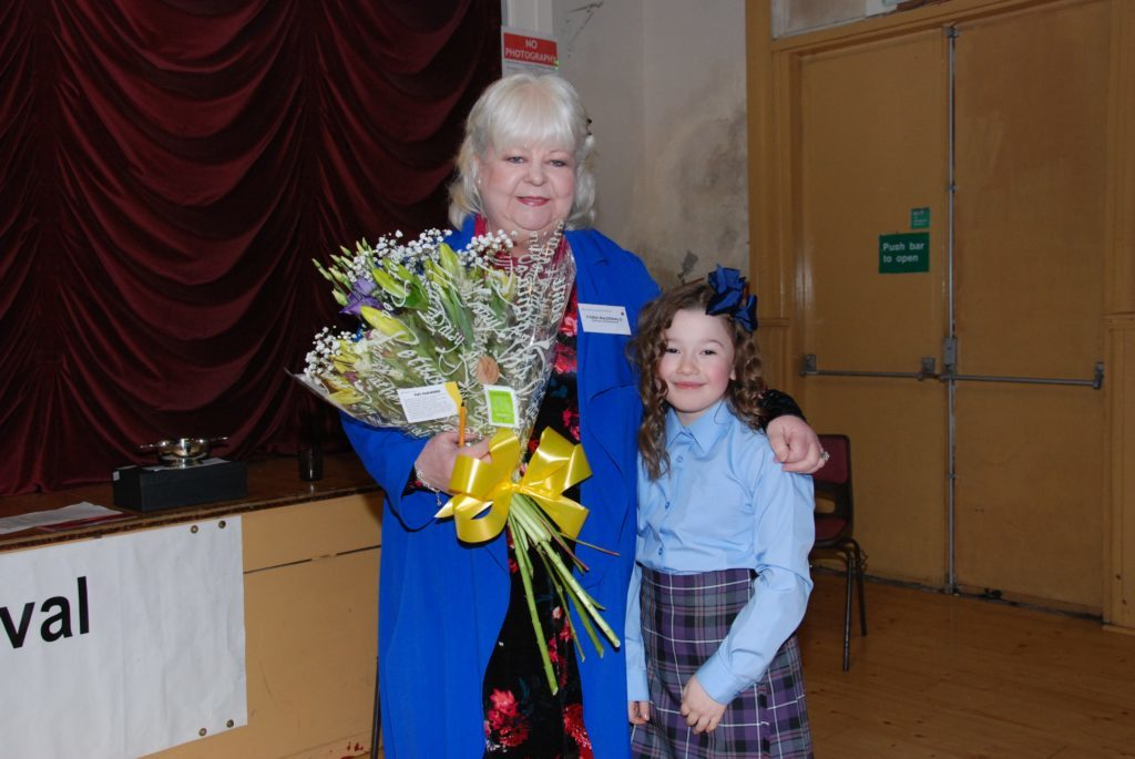 Festival co-ordinator Fiona MacDonald is presented with a bouquet by Feorlin Renton from Inveraray.