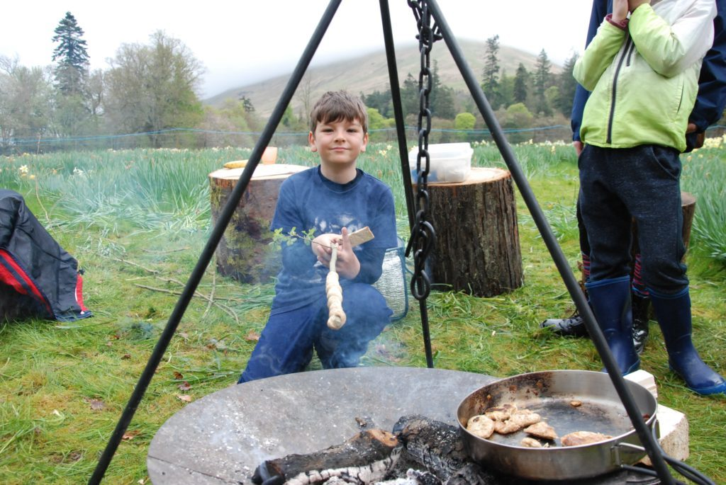 Eight-year-old Joseph Brown from Tarbert cooks bread over an open fire under the watchful eye of mum Nicky. 06_a19ScapaFest20