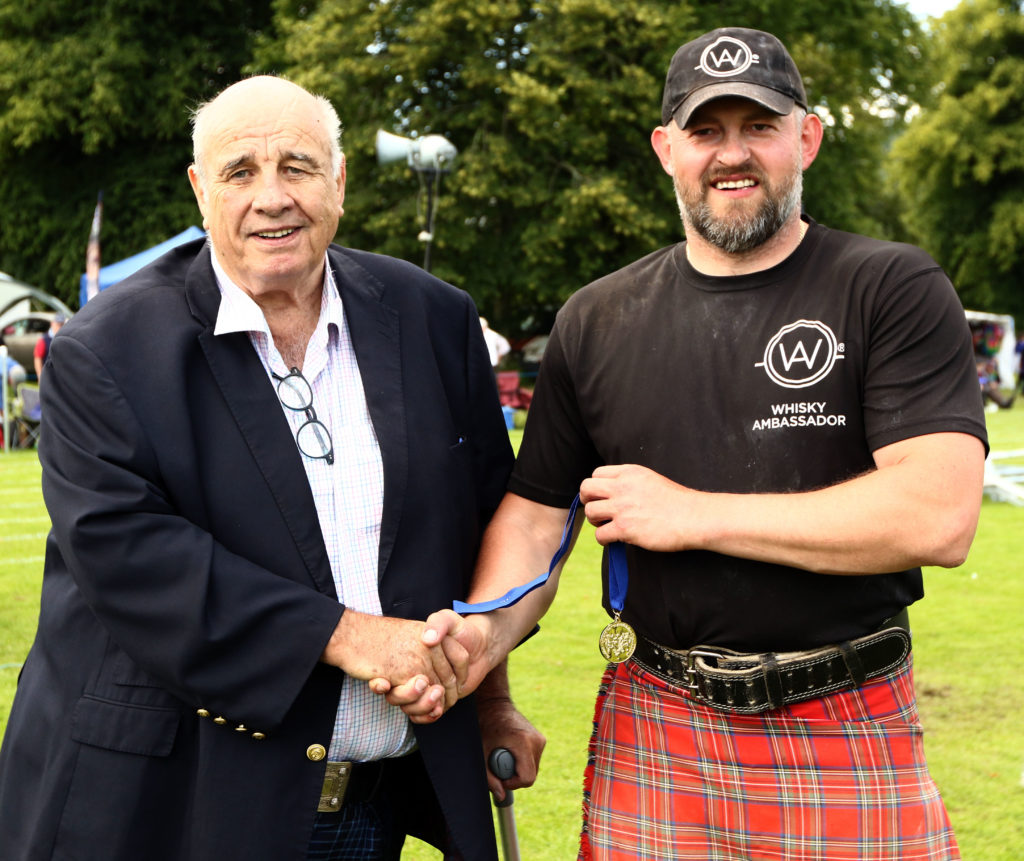 Donald Clark, owner of the George Hotel in Inveraray and sponsor of the World Caber Championships, presents Lukaz Wenta with the gold medal for winning the caber tossing event. Photograph: Kevin McGlynn