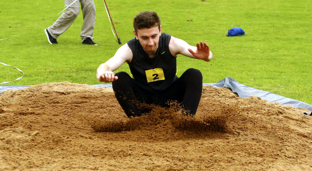 Ben Coates of Oban hits the sand in the long jump. Photograph: Kevin McGlynn
